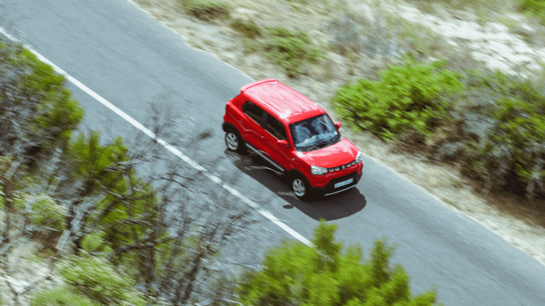 Aerial view of Red Suzuki S-presso driving on the road