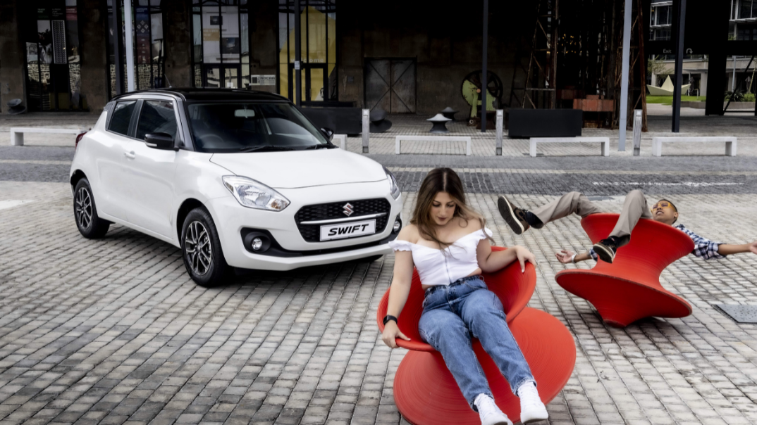 Suzuki Swift with two young adults in the foreground